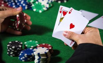 Händer som håller spelmarker och spelkort.